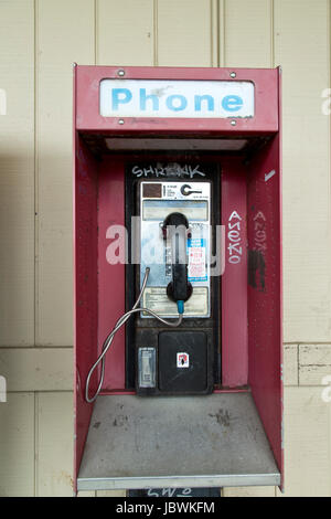 Abandoned coin operated public pay telephone with coin release slot, old shopping center, California, United States. - Stock Photo