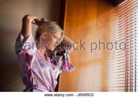 Young woman standing beside window, putting hair up - Stock Photo