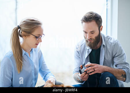 Female and male designers reviewing digital camera photographs in design studio - Stock Photo