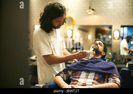 Hairdresser in barbershop giving customer wet shave - Stock Photo
