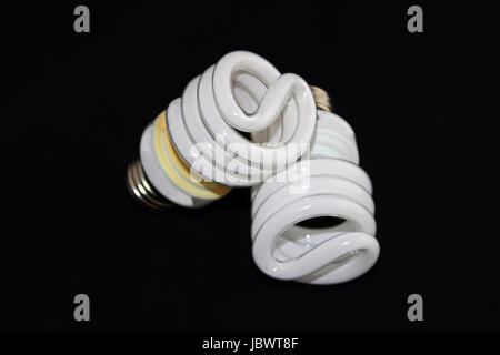 Closeup of two fluorescent light bulbs isolated on a black background. - Stock Photo