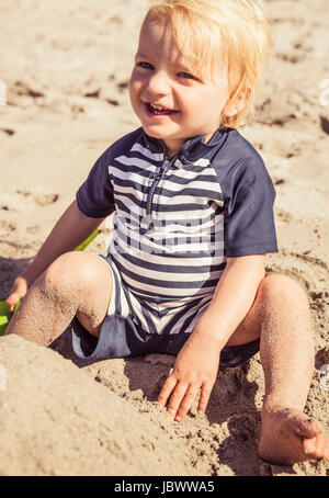 Portrait of young boy, sitting on beach, smiling - Stock Photo