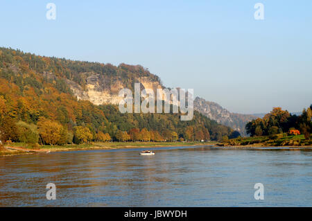 Die Elbe im deutschen Teil des Elbsandsteingebirges; steile Felsen und bunte Laubwälder; auf dem Fluss ein Boot - Stock Photo