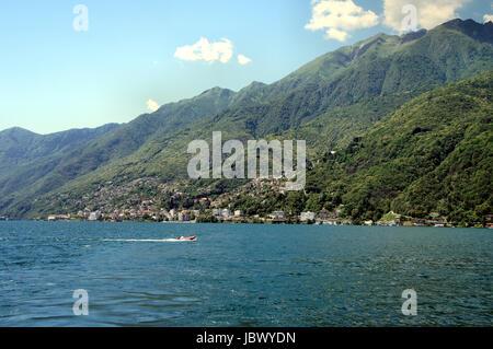 Auf dem Lago Maggiore im Tessin, Schweiz; kleine Städte, Häuser und bewaldete Berge; im Vordergrund ein Boot auf - Stock Photo