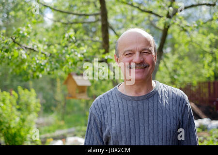 Mature man sitting in garden near apple tree in countryside - Stock Photo