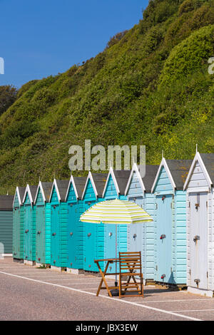 Table, chair and parasol outside beach huts in shades of turquoise blue green at Bournemouth in June - Stock Photo