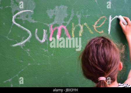 The word 'summer' written on a green board by a girl - Stock Photo