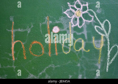 The word 'holiday' written on a green wall and a flower drawn next to it - Stock Photo