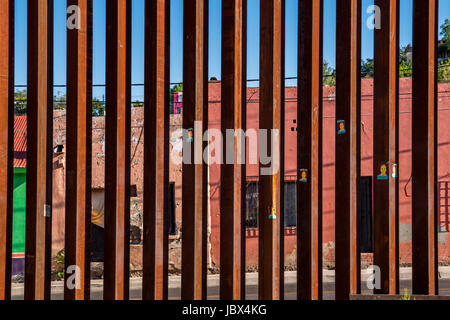 International border between United States and Mexico in Nogales, Arizona; closeup of steel border fence - Stock Photo