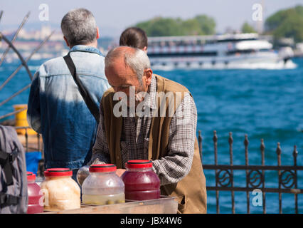Old man selling drinks and foods on the karakoy pier in Istanbul. Eating on the street is part of local life here - Stock Photo