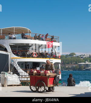 Old man selling drinks and foods on the karakoy pier in Istanbul in front of a leaving ferry boat.Eating on the - Stock Photo