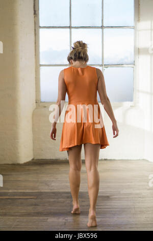 Rear view of a young blonde Caucasian woman wearing a short orange summer dress walking towards the window barefooted - Stock Photo