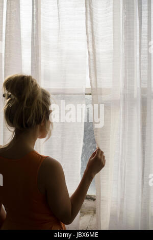Rear view of a blond Caucasian woman standing by the window looking away - Stock Photo
