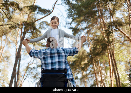 Low angle photo of strong man that looking at his kid - Stock Photo