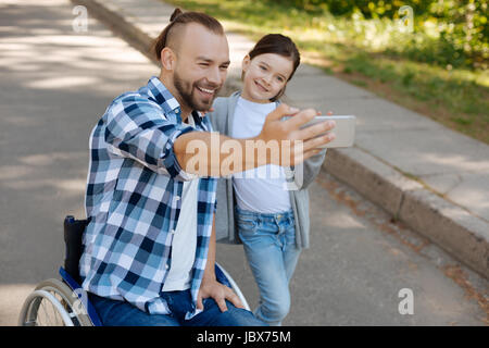 Pretty girl taking photo on telephone with her dad - Stock Photo