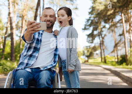 Delighted man holding new telephone in right hand - Stock Photo
