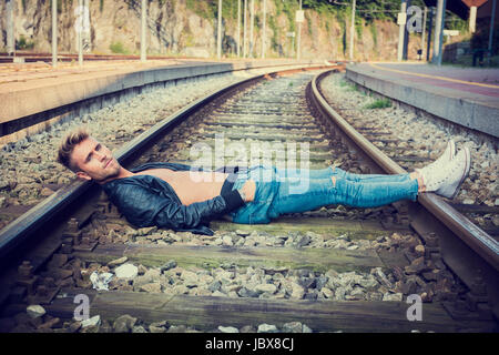 Confident stylish young man with hands in pockets lying on train rails. - Stock Photo