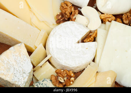 assortment of cheeses on wooden plate close up - Stock Photo