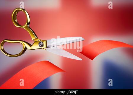 Golden scissors cutting red ribbon, symbolising brexit - Stock Photo