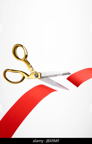 Golden scissors cutting red ribbon/ tape - Stock Photo