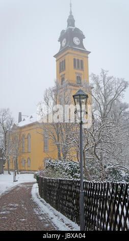Eine Kirche im Erzgebirge in Sachsen an einem grauen Wintertag, gelbes Gebäude, Weg mit Laterne und kahle Bäume - Stock Photo