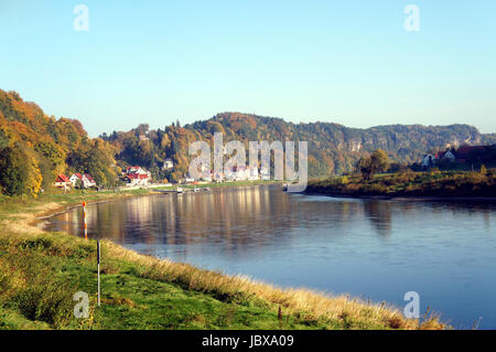 Die Elbe im deutschen Teil des Elbsandsteingebirges; steile Felsen und bunte Laubwälder; am Ufer ein kleiner Kurort - Stock Photo