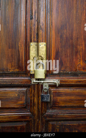 Brass door plates and padlocks on wooden door, Shuhe old town, Yunnan, China - Stock Photo