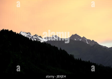 Mountain silhouettes in the austrian apls during sunset. - Stock Photo