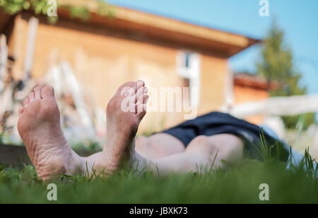 Man laying on grass field. He relax on nature in summer. Look up on sky - Stock Photo