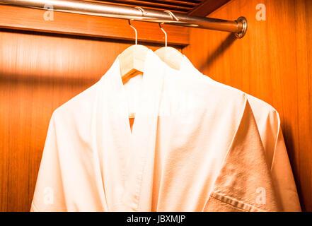Bathrobes hanging on wooden hangers in wardrobe - Stock Photo