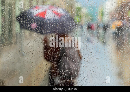 Abstract blurred silhouette of girl under umbrella, city street seen through raindrops on window glass, blurred - Stock Photo
