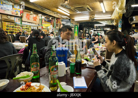 Horizontal view inside a bustling streetfood restaurant in Hong Kong, China. - Stock Photo