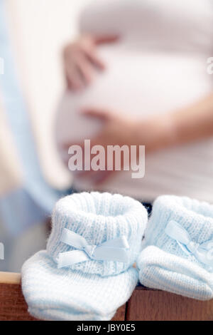 pregnant woman in the nursery with baby shoes - Stock Photo