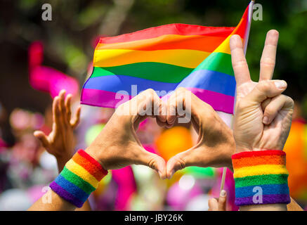 Supporting hands make peace and heart signs in front of a rainbow flag flying on the sidelines of a summer gay pride - Stock Photo
