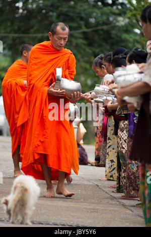 THAILAND, SANGKHLA BURI - NOVEMBER 21, 2012: Buddhist monks collecting alms and food given by the local people in - Stock Photo