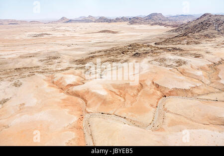 Aerial panoramic view of dried up, dessicated river beds and mountainous terrain in the Namib Desert by the Skeleton - Stock Photo