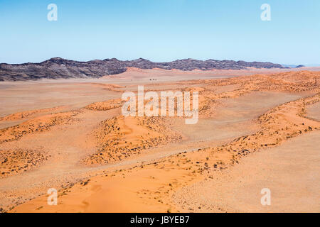 Typical bleak, desolate, arid mountainous terrain of the Namib Desert with ochre sand dunes on the Skeleton Coast, - Stock Photo