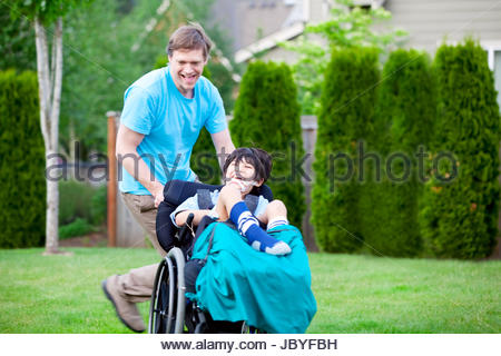 Father running with disabled son in wheelchair - Stock Photo