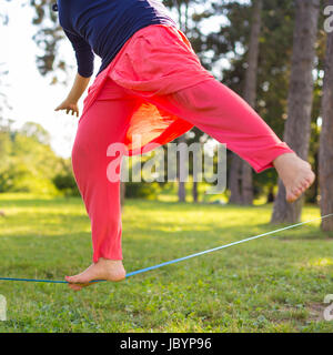Slacklining is a practice in balance that typically uses nylon or polyester webbing tensioned between two anchor - Stock Photo
