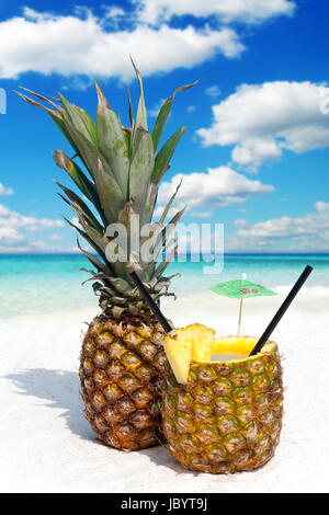 Ananasfrucht und Cocoktail am tropischen Sandstrand - Stock Photo