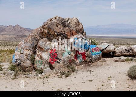 Graffiti spray painted on boulder in American Southwest desert landscape - Mojave desert, California USA - Stock Photo