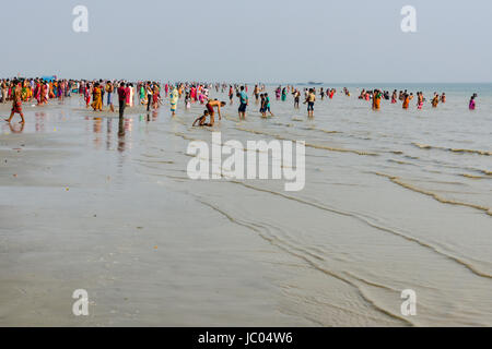 Hundreds of pilgrims are gathering on the beach of Ganga Sagar, celebrating Maghi Purnima festival - Stock Photo