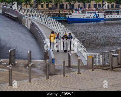 Young people on Gateshead Millenium bridge - Stock Photo