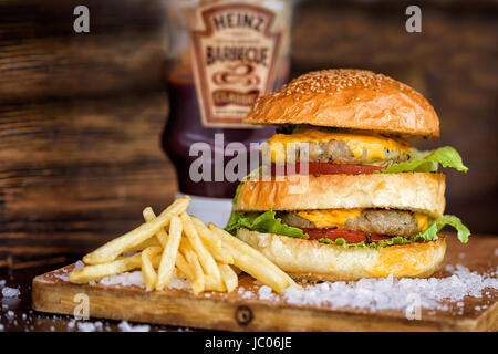 Homemade Maxi Burger with grilled beef steak, lettuce, cheese, tomato, onion, barbecue sauce, honey mustard, fries - Stock Photo