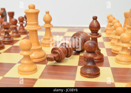 King at the foot of various pieces on the chessboard - Stock Photo