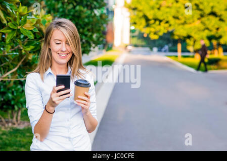 Close up portrait of a joyful businesswoman using her smartphone and carrying work folders, standing against a sunny - Stock Photo