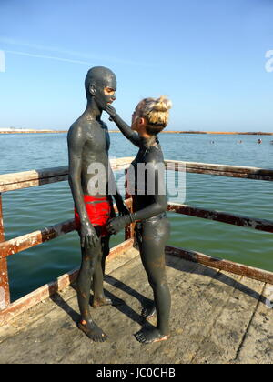 A girl who smears a boy with therapeutic mud from the Salinas and Arenales of San Pedro del Pinatar, Spain - Stock Photo