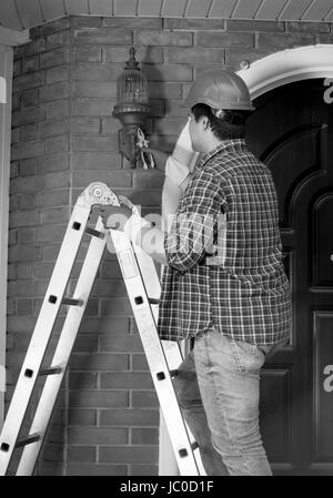 Black and white photo of electrician in helmet repairing outdoor lights - Stock Photo