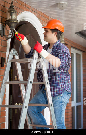 Male electrician in hardhat standing stepladder and repairing lamp on house outdoor wall - Stock Photo