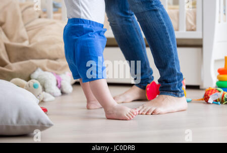 Closeup photo of adorable baby's and mother's feet on floor at living room - Stock Photo